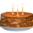 Honey cake with lighting candles - Stock Photo