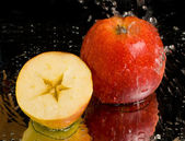 Full apple and half with water splashing — Stock Photo