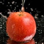 Red apple under water stream — Stock Photo