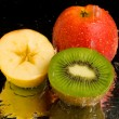 Water spray on kiwi and apples - Stock Photo
