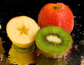 Water spray on kiwi and apples — Stock Photo
