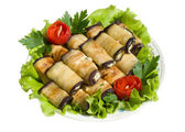 Rolls from eggplant on salad leaves — Stock Photo