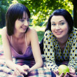 Two girls relaxing in park — Stock Photo