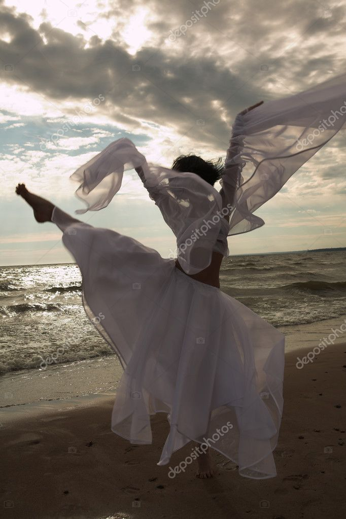 Woman dancing freely on beach