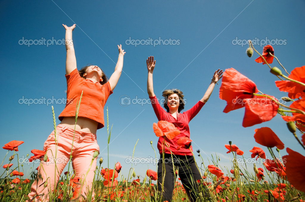 Two girls relaxing in poppy field — Stock Photo #1816373