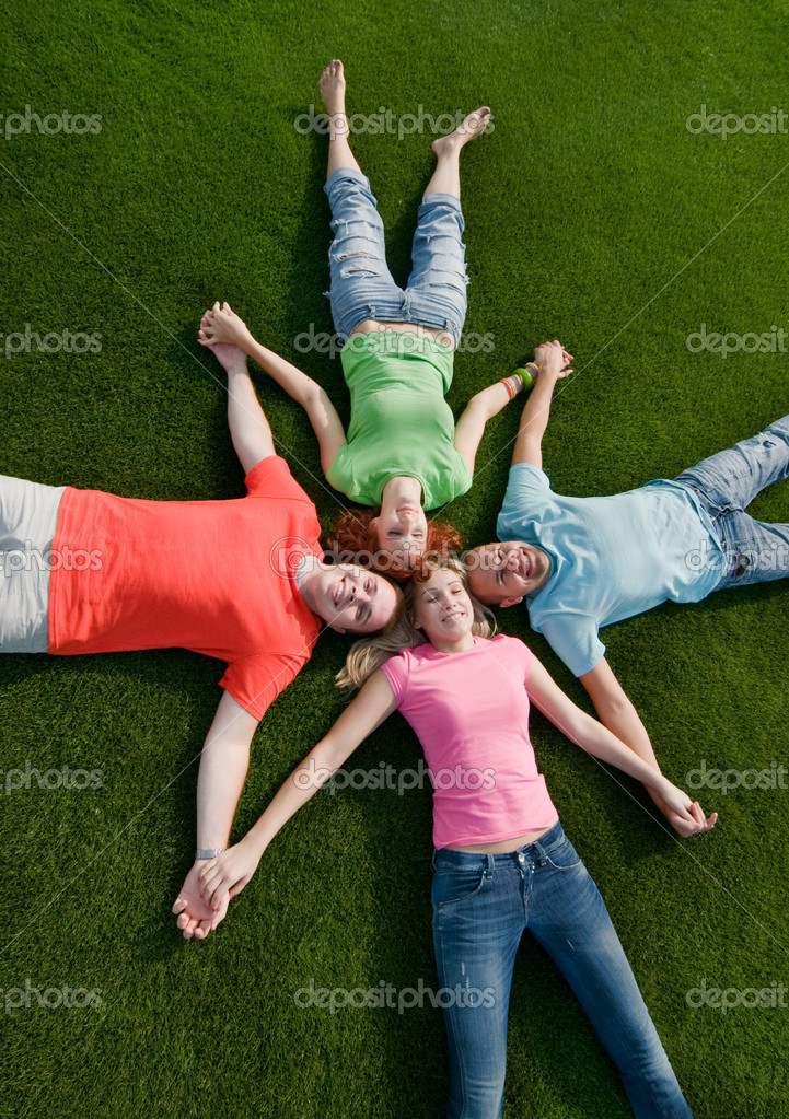 Happy teen friends lying on grass  Stock Photo #1817138