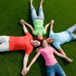 Friends lying on grass — Stok fotoğraf