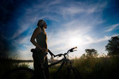 Girl biking at sunrise — Stock Photo
