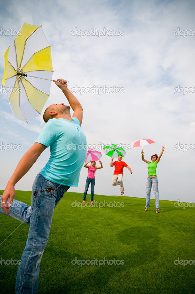 Young friends jumping with umbrellas — Stock Photo #1821501