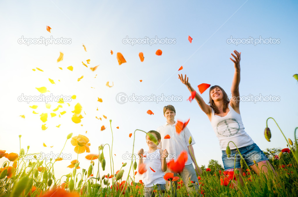 Family in red poppy field — Stock Photo #1827573