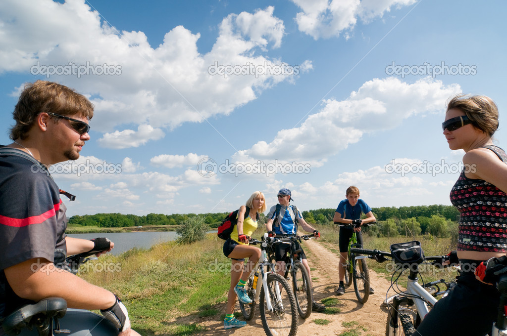 Mixed group of cyclists beside river — Stock Photo #2119151