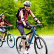Stock Photo: Two girls biking