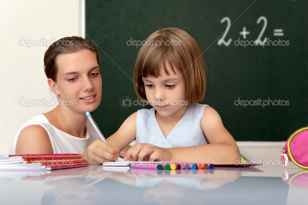 Elementary school pupil working at desk under the supervision of a teacher — Stock Photo #1622433