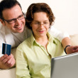 Happy couple shopping online with laptop - Stock Photo