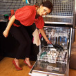 Stock Photo: Young womloading dishwasher