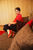 Beautiful woman sitting on sofa — Stok fotoğraf