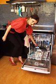 Young woman loading dishwasher — Stock Photo