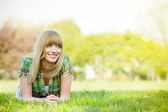 Smiling woman laying on grass — Stock Photo