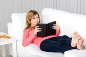 Young woman on sofa lesen — Stockfoto