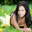 Beautiful woman laying on grass - Stok fotoğraf