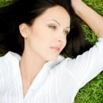 Beautiful woman laying on grass — Stock Photo