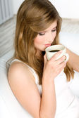 Beautiful woman drinking coffee at bed — Stock Photo