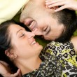 Young happy couple laying on carpet — Stock Photo