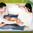 Young happy couple sitting on couch — Stock Photo