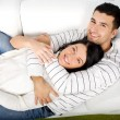 Happy couple laying on couch — 图库照片
