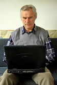 Old man wirh laptop — Stock Photo