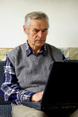 Old man with laptop — Stock Photo