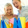 Foto Stock: Two women with bags at shopping.