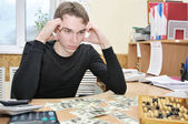 Young man thinking where to spend money — Stock Photo