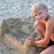 Smiling boy playing on sandy beach — Stock Photo #1798056
