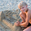 Smiling boy playing on sandy beach — Stock Photo