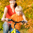 Young happy women and son on bicycle — Stock Photo