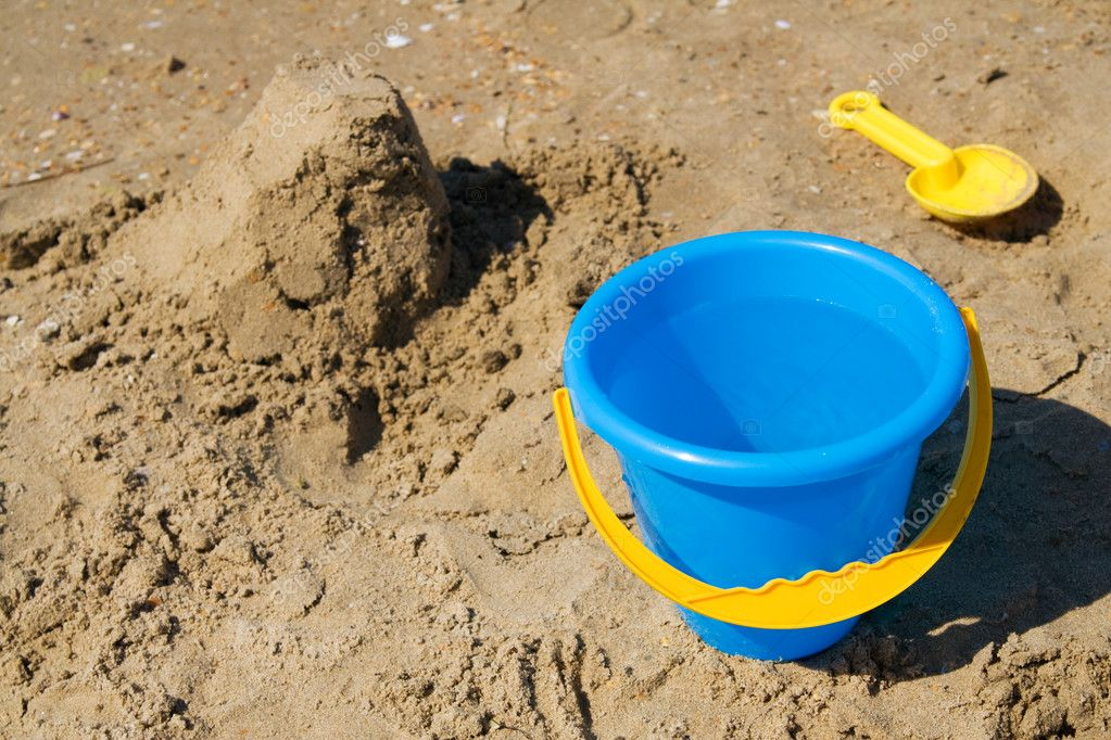 Blue bucket and yellow spade on a beach — Stock Photo #1798118