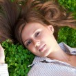 Young nice girl lying on the green grass — Stock Photo