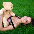 Young girl lying on the green grass with — Stock Photo