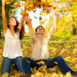 Young couple throwing autumn leaves — Stok fotoğraf