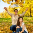 Young couple throwing autumn leaves — Stock Photo #1855436