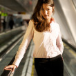 Businesswoman on a moving walkway — Stock Photo