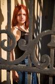 молодая женщина позирует в за решеткой — Стоковое фото