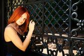 Mladá žena pózuje před roštem — Stock fotografie