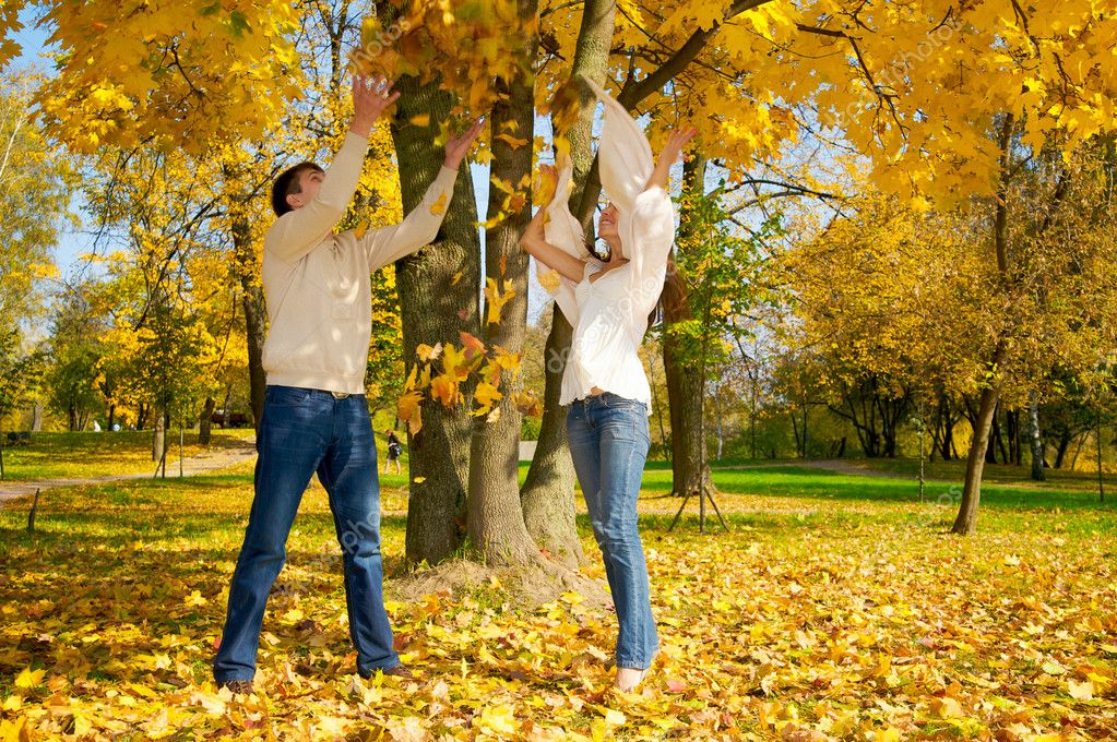 Young happy couple throwing autumn leaves in the air — Stock Photo #1855392