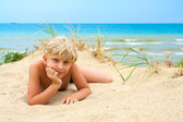 Young blond boy lying on the beach — Stock Photo