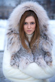 Beautiful young woman in winter fur coat — Stock Photo