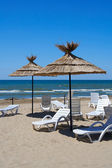Parasols and chaise-longue on a beach — Stock Photo