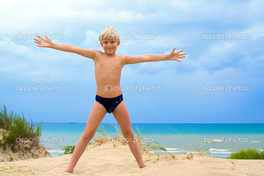 Happy young boy with his arms wide open in the sandy beach  Stock Photo #1913851