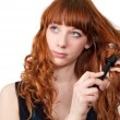 Young redhead woman straightening her hair — Stock Photo